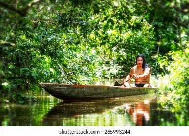 Indigenous Adult Man On Typical Wood Canoe Chopped From A Single Tree Navigating Murky Waters Of Ecuadorian Amazon Primary Jungle
