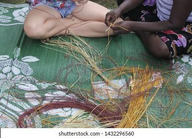 Indigenous Australians aboriginal woman teaching a tourist Aboriginal basket weaving technique.