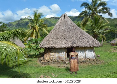 Indigenous Fijian man dressed in traditional Fijian costume, stand outside his Bure hut at Navala village in Ba highlands on Viti Levu island, Fiji. Real people, copy space