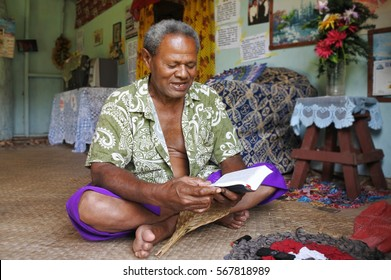 Indigenous Fijian man reads the bible in his home in Fiji.  Fiji was Christianized in the 19th century. Today there are various Christian denominations in Fiji, the majority being Methodist.