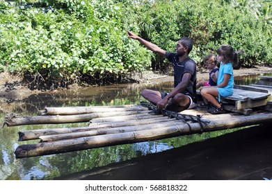 Indigenous Fijian man and two tourist children ride on a traditional Fijian bamboo boat over a water stream in Vanua Levu island, Fiji.