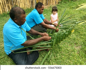 Indigenous Fijian men teach young tourist girl how to create a basket from weaving a Coconut Palm leaves.Travel Fiji concept, Real people copy space