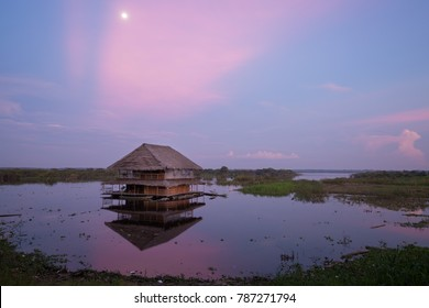 Indigenous floating house at sunset in Iquitos, Peru in the Amazon rainforest