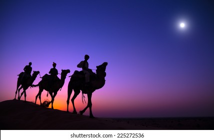 Indigenous Indian men riding through the desert with their camel.