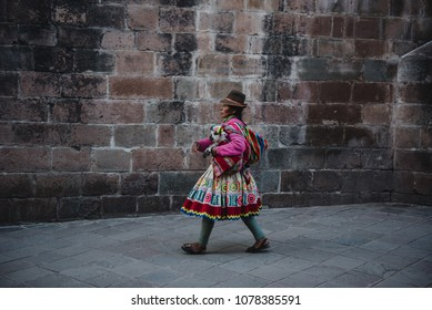 The indigenous people of Peru walking around holding a baby goat in the city of Cusco, Peru. April 22, 2015.