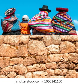 Indigenous Quechua / Inca women chatting with a young boy while seated on an ancient Inca Wall in Chincheros near the city of Cusco, Peru, South America.