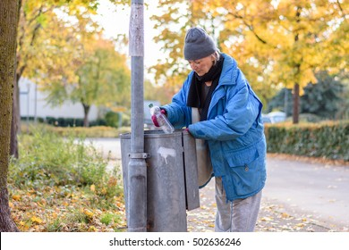 Indigent senior woman scrounging through a bin for food on an urban autumn street in a concept of homelessness and poverty