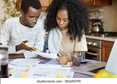 Indignant African husband gesturing with pencil, reproaching his wife for doing mistake while calculating bills, woman looking at piece of paper with serious frustrated expression. People and finances