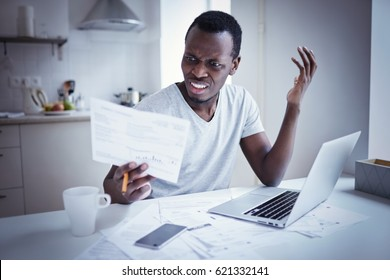 Indignant angry irritated young african american man looking at utility bill, frustrated about high taxes, worried about troubles with mortgage payment to bank, having serious problems with debt