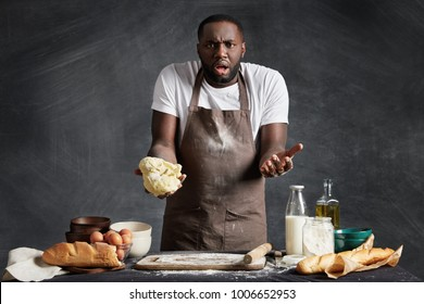 Indignant bewildered dark skinned male chef holds dough, can`t understand what he done wrong or not according recipe, feels frustarated and despondent, poses near kitchen table with products