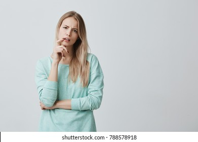 Indignant blonde female student being dissatisfied with results of exam or competition, can`t believe she made mistakes. Tired woman listens in displeasure lecture, keeps finger on opened mouth