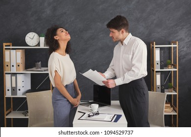 Indignant boss showing mistake in papers to dreaming african-american secretary, ignoring him, standing at workplace in office, copy space