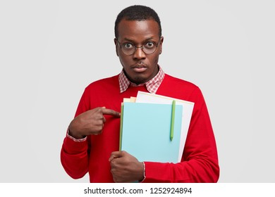 Indignant male professor points at himself, asks about his duties, carries textbook, wears casual red sweater, going to conduct seminar for scientists isolated on white wall. People, science, studying