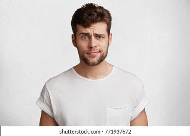 Indignant puzzled male model with attractive appearance frowns face in bewilderment, can`t understand material, dressed casually, prepares for exams at home, poses against white background