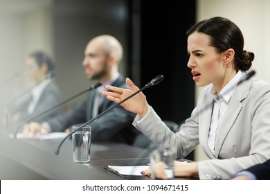 Indignant young female politician shouting into microphone at conference or political summit