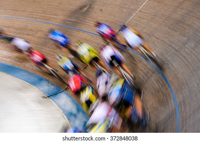 Indiscernible pack of track cyclists racing past on the turn of a velodrome