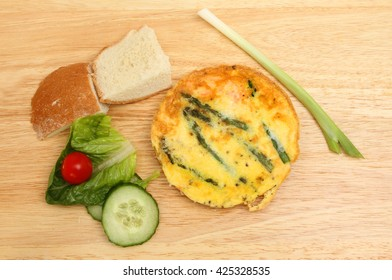 Individual asparagus Frittata with bread and salad on a wooden chopping board