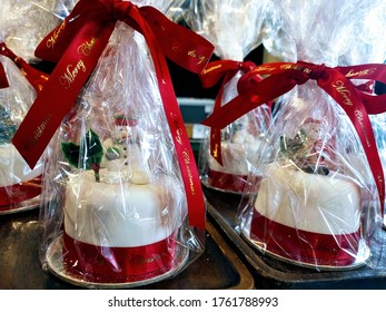 Individual Christmas cakes for sale at a bakery in Melbourne Australia with snowmen on top and wrapped in festive holiday packaging