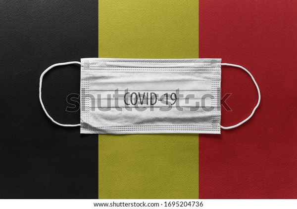 An individual face medical surgical mask on Belgium national flag Background. Health mask. Protection against COVID-19 virus, influenza, SARS. Save Belgium from Coronavirus