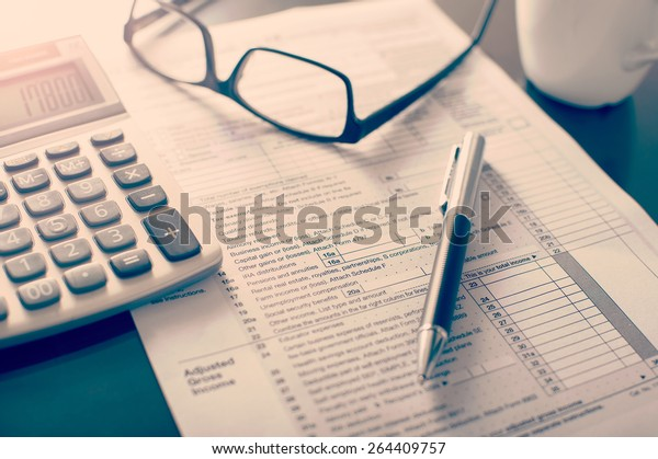 Individual income tax return form, glasses, pen and calculator on desk