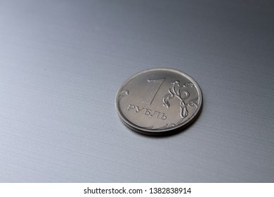 Individual russian rouble coins on a grey background.