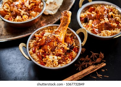Individual servings of spicy Arabian kabsa with long grained rice, vegetables and meat with dried star anise and cinnamon ingredients alongside
