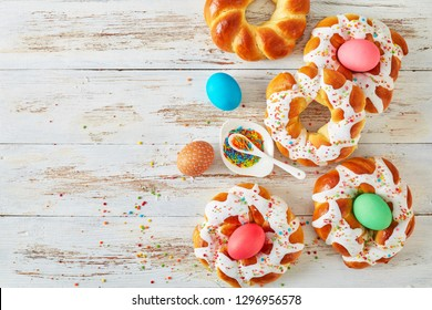 individual sweet Italian braided Easter Bread Rings glazed around dyed egg and topped with colorful sprinkles on a wire rack, on an old white wooden table, view from above, copy space