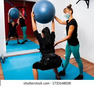 Individual training with personal trainer wearing protective mask on her face. After covid19 , precaution measures in gyms