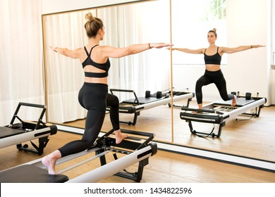 Individual woman in black doing lunge stretch pilates series while standing on reformer bed in workout room