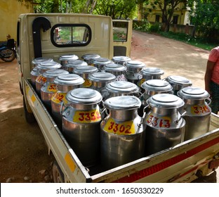 Individually numbered stainless steel milk cans filled with raw milk loaded in a mini truck in India