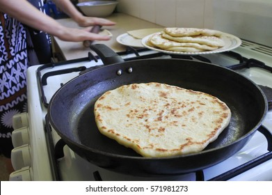 Indo-Fijian woman cooking homemade Naan bread in the kitchen. Indian food.