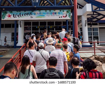 INDONESIA – 6 MAR 2020 – A crowd of tourists disembark a ferry boat from Singapore to Bintan Island and head towards the Bandar Bentan Telani ferry terminal. Bintan is a popular tourist destination