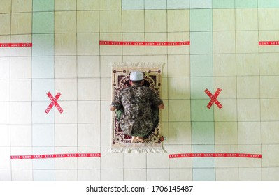 Indonesia April 17 2020 : Social distancing covid 19 young people praying in Mosque Indonesia, physical distancing in pray, Corona pandemi saat Sholat Indonesia, Pray at home