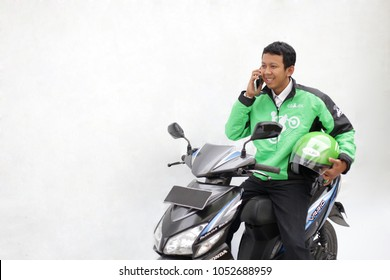 indonesia asian man work as a commercial motorcycle taxi driver grab, gojek and uber. march 19, 2018. Yogyakarta Indonesia.