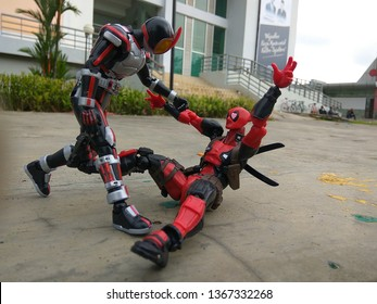 Indonesia - August 06, 2017 : Masked Rider figure and Deadpool playing outdoor in Park of Samarinda, Indonesia. Masked Rider is famous Television series in Japan and many country