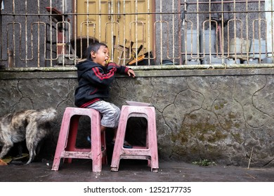 INDONESIA, BALI - AUGUST 2014: A portrait of an unidentified poor child from a rural part of Bali, Indonesia. Children from undeveloped countries cannot afford education and thus live deprived life.