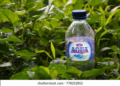 Indonesia - December 03, 2017: bottle of Aqua is an Indonesian brand of mineral water on green grass owned by Danone since 1998