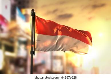 Indonesia Flag Against City Blurred Background At Sunrise Backlight 3D Rendering