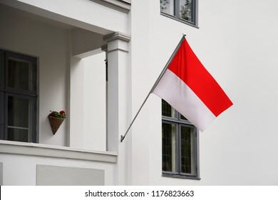 Indonesia flag. Indonesian flag hanging on a pole in front of the house. National flag waving on a home displaying on a pole on a front door of a building. Flag raised at a full staff.