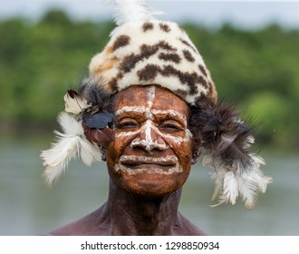 INDONESIA, IRIAN JAYA, ASMAT PROVINCE, AMANAMKAY VILLAGE - MAY 22: The Portrait Asmat warrior with a traditional painting and coloring on a face. On May 22, 2017  Amanamkay Village, Asmat province, In
