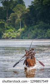 INDONESIA, IRIAN JAYA, ASMAT PROVINCE, AMANAMKAY VILLAGE - MAY 22: Men Asmat tribe float in a canoe on the river. On May 22, 2017 Amanamkay Village, Asmat province, Indonesia