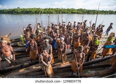 INDONESIA, IRIAN JAYA, ASMAT PROVINCE, AMANAMKAY VILLAGE - MAY 22: Men of the Asmat tribe on a canoe at the village pier. On May 22, 2017 Amanamkay Village, Asmat province, Indonesia