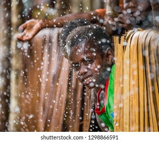 INDONESIA, IRIAN JAYA, ASMAT PROVINCE, AMANAMKAY VILLAGE - MAY 22: A boy from the tribe of Asmat in a village house under a tropical rain. On May 22, 2017 Amanamkay Village, Asmat province, Indonesia