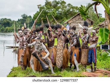 INDONESIA, IRIAN JAYA, ASMAT PROVINCE, AMANAMKAY VILLAGE - MAY 22: A group of warriors of the tribe Asmat with spears on the river bank posing in front of the photographer. On May 22, 2017 Amanamkay V