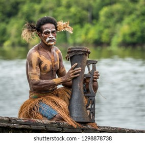 INDONESIA, IRIAN JAYA, ASMAT PROVINCE, AMANAMKAY VILLAGE - MAY 22: Warrior of the Asmat tribe in war paint and with a drum in his hands. On May 22, 2017 Amanamkay Village, Asmat province, Indonesia