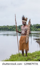 INDONESIA, IRIAN JAYA, ASMAT PROVINCE, AMANAMKAY VILLAGE - MAY 22: Warrior of the tribe Asmat stands with a shield and a spear in his hands in a traditional war paint. On May 22, 2017 Amanamkay Villag