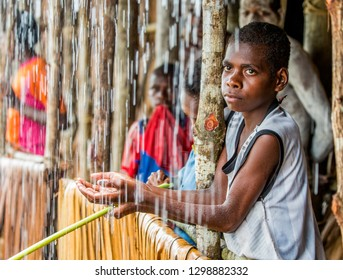INDONESIA, IRIAN JAYA, ASMAT PROVINCE, AMANAMKAY VILLAGE - MAY 22: Boy from the tribe of Asmat in a village house under a tropical rain. On May 22, 2017 Amanamkay Village, Asmat province, Indonesia