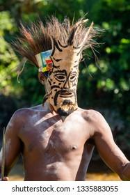 INDONESIA, IRIAN JAYA, ASMAT PROVINCE, AMANAMKAY VILLAGE - 13 JUNE 2016: Warrior of the Asmat tribe in ritual mask. On June 13, 2016 Amanamkay Village, Asmat province, Indonesia