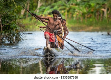INDONESIA, IRIAN JAYA, ASMAT PROVINCE, AMANAMKAY VILLAGE - 13 JUNE 2016: Warriors of the Asmat tribe swim in a traditional canoe on the river among the jungle. On June 13, 2016 Amanamkay Village, Asma