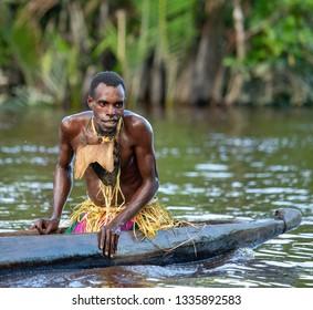 INDONESIA, IRIAN JAYA, ASMAT PROVINCE, AMANAMKAY VILLAGE - 13 JUNE 2016: Warrior of the Asmat tribe is sitting in a traditional canoe. On June 13, 2016 Amanamkay Village, Asmat province, Indonesia
